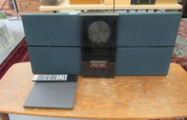 A Bang & Olufsen BeoSound Century CD and cassette player with integral speakers and a remote