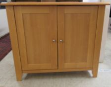 A modern beech cupboard with a pair of doors, enclosing a shelf,