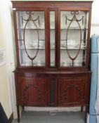 An Edwardian mahogany display cabinet with a pair of glazed doors, over a bow front,