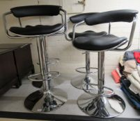 A set of four modern height adjustable bar stools,
