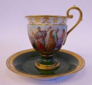 An early 20thC Vienna porcelain pedestal cup and saucer with a scrolled handle,