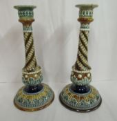 A pair of Doulton Lambeth blue, green and brown glazed stoneware candlesticks, decorated in moulded,