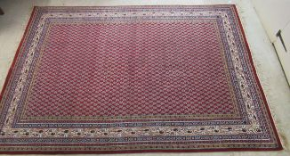A Persian rug, decorated with repeating small trees, bordered by stylised foliate designs,