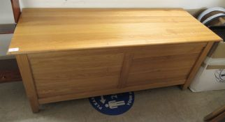A modern pine chest with straight sides and a hinged lid, enclosing two drawers,