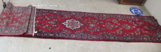 A Persian runner, decorated with floral designs,