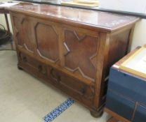 A 1930s oak mule chest with a hinged lid, over a tri-panelled front and two base drawers,