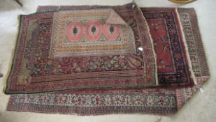 Four Persian and other rugs, mostly decorated with floral and foliate designs,