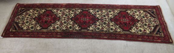 A Persian runner, decorated with three diamond shaped motifs,