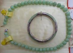 A Hong Kong/Chinese jade hinged bangle with silver coloured metal mounts;