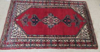 A Persian rug, decorated with stylised designs,