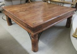 A modern Indonesian teak coffee table, raised on turned legs and wrought iron bracket supports 15.