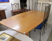 A modern cherrywood dining table, the top with elliptical sides,