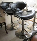 A pair of modern black hide upholstered breakfast stools,