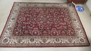 A Persian rug, profusely decorated with flora and foliage,