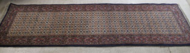 A Persian runner, decorated with repeating stylised designs,