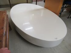 A modern white laminate oval coffee table,