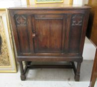 A 1930s oak hall cabinet with a single panelled door, raised on turned,