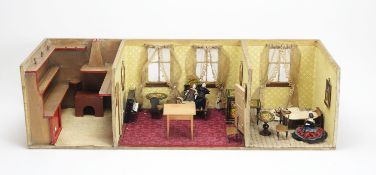 An antique open doll's house with three rooms, furniture and other items.