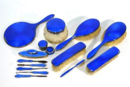 A matched silver and blue basse-taille enamel-mounted dressing table set