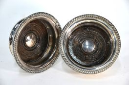 A pair of silver bottle coasters with gadrooned rims and turned wood bases