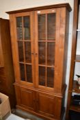 A stained teak two section bookcase cabinet,
