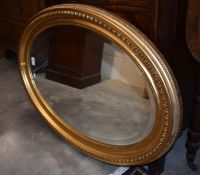 A bevelled oval wall mirror