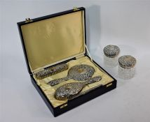 A four-piece embossed silver brush set with hand mirror, in fitted presentation case