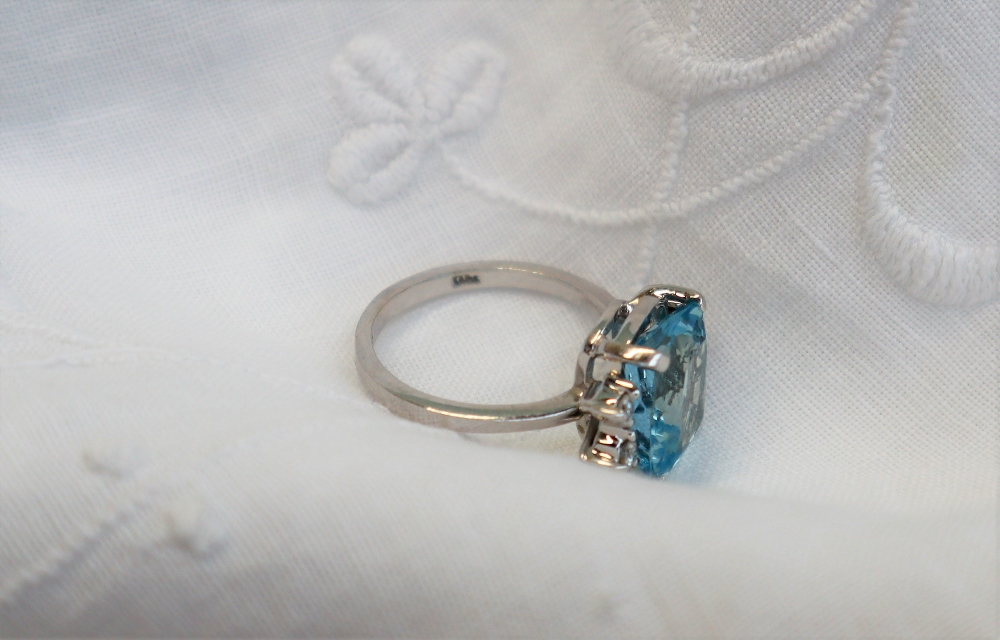 Lot 39 - An aquamarine and diamond ring, the central cushion shaped aquamarine approximately 11 x 9mm,