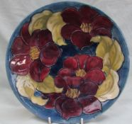 A Moorcroft pottery plate, decorated in the clematis pattern,