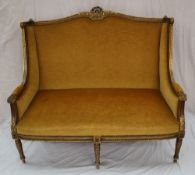 A French gilt decorated two seater settee, with a gilt leaf moulded scrolling back,