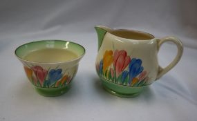 A Clarice Cliff milk jug and sugar bowl, decorated in the Crocus pattern with a green border,