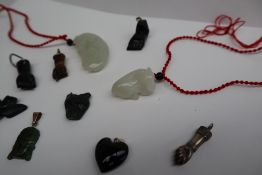 A jade pendant carved as a buffalo, on a red cord, together with another carved as a horse,