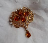 A citrine and pearl brooch of scrolling form set with four oval faceted citrines surrounded by