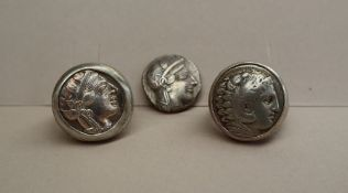 A white metal Greek coin, with the head of Athena to one side and an owl to the other,