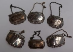 A set of three Elizabeth II silver wine labels, of oval form, decorated with flowers and leaves,