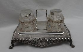A late Victorian silver desk standish, with a shell leaf and dart border on four claw feet,