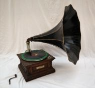 An oak cased gramophone, the case carved with flowerheads and leaves,