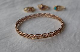 A Clogau 9ct yellow gold bangle composed of four inter wound strands,