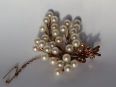A yellow and white metal brooch, set with thirty pearls each approximately 7mm in diameter,