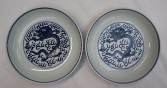 A pair of Chinese porcelain dishes, decorated with dragons amongst clouds,