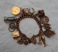 A 9ct yellow gold charm bracelet, set with numerous charms including a pub, slippers, 13, crown,