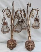 A pair of brass three branch wall sconces, with lion mask heads and scrolling terminals,
