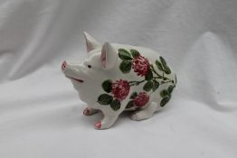 A Wemyss ware seated pig painted with flowers, painted marks Exon 1373 B Adams,