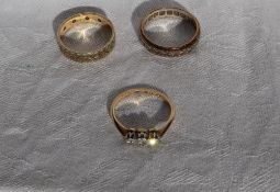 A three stone diamond ring set with old round cut diamonds to a 9ct gold setting and shank and two