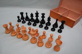 A turned wooden chess set, with weighted pieces, one side ebonised, King 9.5cm high, pawn 4.