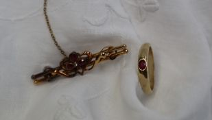 A 9ct yellow gold band with a central oval faceted ruby, size O 1/2,