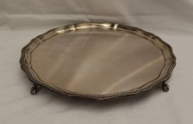 An Elizabeth II silver salver, with a beaded rim and shaped edge on four claw and ball feet,