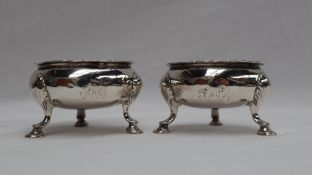 A pair of George III silver cauldron table salts, with a flared rim on cabriole legs,