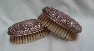 A pair of Elizabeth II silver backed hair brushes decorated with scrolls and leaves, Birmingham,