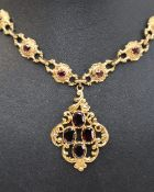 A 9ct yellow gold necklace, the pendant drop set with four oval faceted garnets,